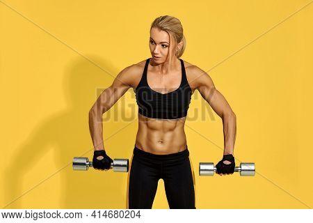 Sporty Woman In Black Sportswear Training With Dumbbells