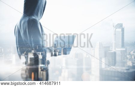 Theft Online Concept With Hacker Back Silhouette With Laptop And Foggy City Background. Mock Up, Dou