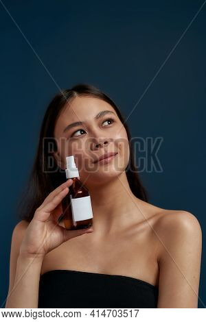 Young Asian Girl With Oil To Moisturize The Skin Standing On A Dark Background. Beautiful Girl With