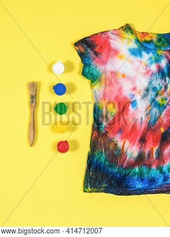 A Paintbrush, Jars Of Colorful Paint, And A Tie Dye T-shirt On A Yellow Background. Staining Fabric
