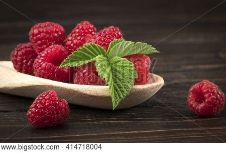 Fresh Raspberry In Wooden Spoon / Close Up Red Raspberries Fruit And Green Leaf On Wood Background.