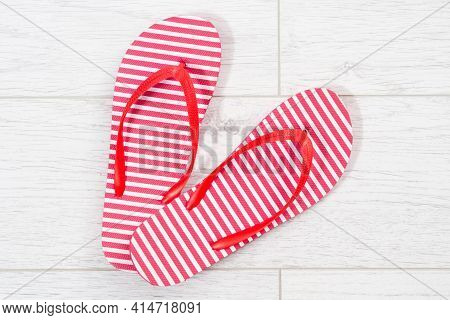 Red Flip Flops On A White Wooden Background Close Up