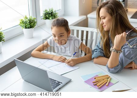 Teenage Girl Doing Homework Online At Home. Mom Closely Monitors The Correctness Of Homework.