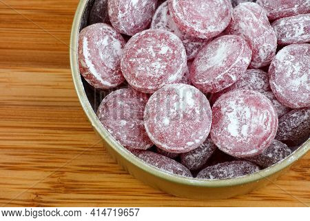 Sour Cherry Drops. Hard Candy With A Sour Flavor With Icing Sugar In A Tin Can. Close Up.