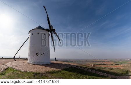 Whitewashed Historic Windmill Typical Of The La Mancha Region Of Central Spain Under A Blue Sky