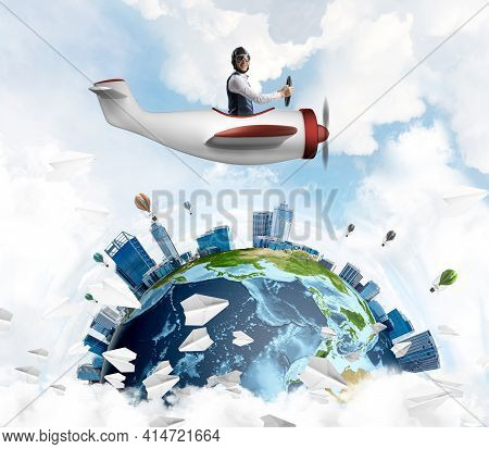 Cheerful Young Pilot Sitting In Cabin Of Small Airplane. Funny Man In Aviator Hat With Goggles Drivi