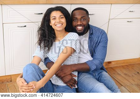 Happy Joyful Mixed-race Black Couple Husband And Wife Sitting On Modern Kitchen Floor And Hugging, S