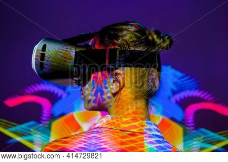 Woman Using Virtual Reality Headset, Looking Left At Interactive Technology Exhibition With Multicol