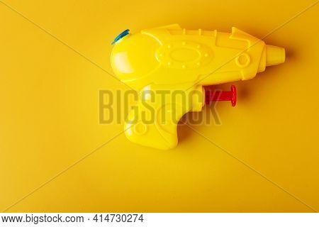 Plastic Water Gun On Yellow Background. Toy Squirt Pistol.