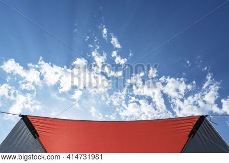 Umbrella Protects From Sun Light Ans Sunrays And Crested Sunshade, Bright Blue Sky And Clouds. Summe
