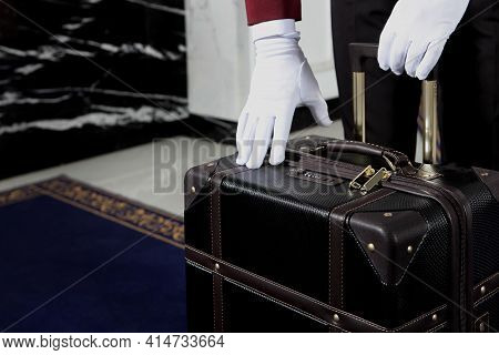 Doorman Is Holding A Suitcase. Unrecognizable Photo. Only White-gloved Hands. Hotel Service. Hotel B