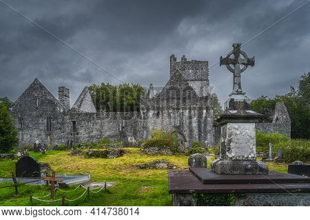 Ancient Graveyard With Celtic Cross Tombstone And Ruins Of 15th Century Muckross Abbey, Killarney Na