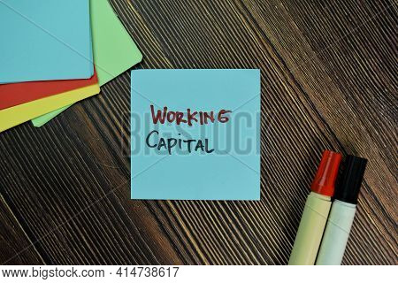 Working Capital Write On Sticky Notes Isolated On Wooden Table.