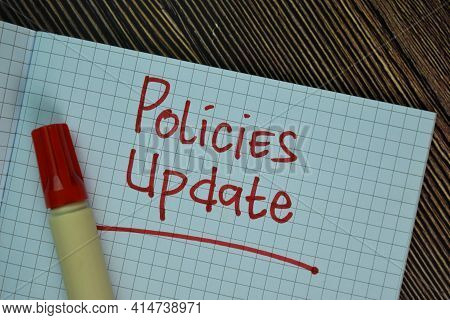 Policies Update Write On A Book Isolated On Wooden Table.