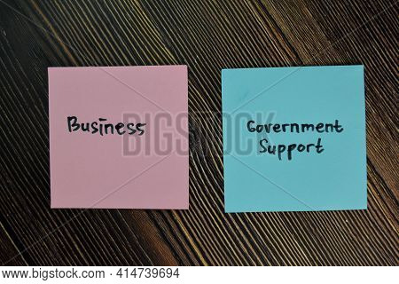 Business And Government Support Write On Sticky Notes Isolated On Wooden Table.
