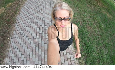 Sportswear Runner Woman Doing Jogging In Town Park Holding A Selfie Mobile Camera. Fit Woman On A Co