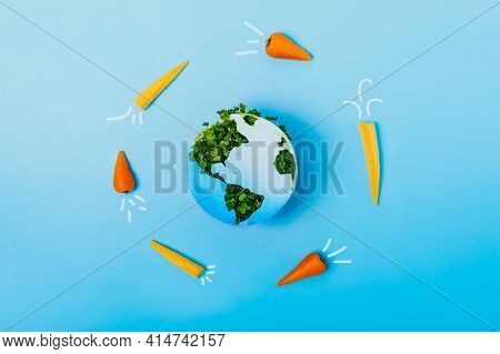 Creative Veganism And Earth Day Concept. Rockets Of Carrots And Baby Corn Flying Around Planet Earth