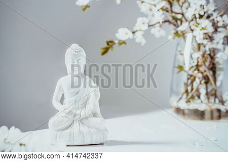 Decorative White Buddha Statuette With Blooing Tree Branches In The Vase On The White Background. Me