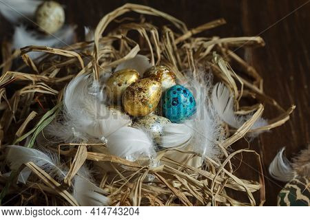 Gilded And Painted Easter Eggs In A Nest Of Twigs,straw And Feathers. Close-up, Selective Focus. Rus