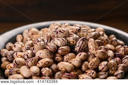 Colored Haricot Beans In Dark Bowl On Wooden Table. Close Up.