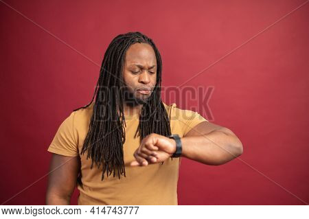 Serious Confused Young African American Man Perfectionist With Dreadlocks Isolated On Red Looking An
