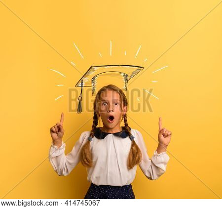 Young Student Is With Shocked Expression And Indicates A Graduation Hat. Yellow Background