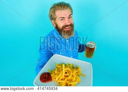 Smiling Man With Potato Fries And Beer. French Fries Potato. Bearded Male With Potatoes Fries And Ke