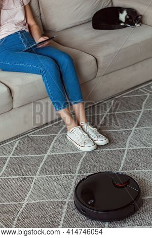 Robot Vacuum Cleaner Cleaning Carpet, Woman Using Tablet And Joy Rest And Cat Sitting On The Sofa Ho