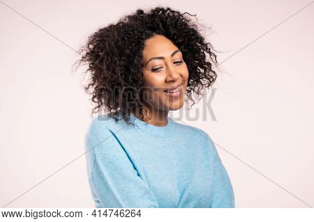 Modest African Woman In Blue Basic Sweater On White Studio Background. Girl Looks Aside, Shy.