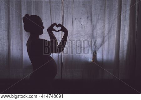 Pregnant Woman Shows A Hand Gesture Sign Of Love On Valentine Day, Silhouette Against The Background
