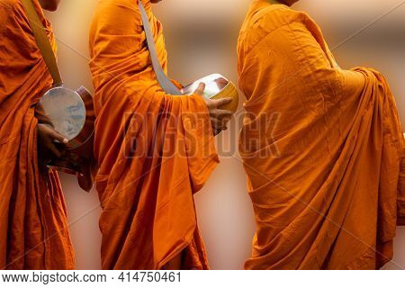 Three Monks Holding A Bowl. Buddhist Important Days.blurred Background
