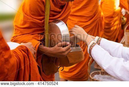 Thai People Are Offering Food To The Monks In The Bowl. On Buddhist Important Days