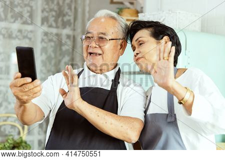 Portrait Of An Elderly Asian Couple Doing Facetime Video Calling With A Smartphone At Home Using The