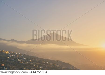 View Of Teide At Sunset With Calima With A Village On The Hillside. Travel Destination