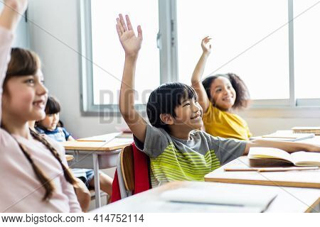 Diversity Of Elementary School Students Raise Their Hands To Answer Teacher Questions. Back To Schoo