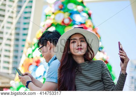 A Picture Of An Asian Woman Leaning On Her Boyfriend Who Is Using A Smartphone, Her Eyes Looking At