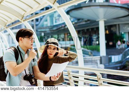 Portrait Of Young Asian Male And Female Tourists Viewing Map Of Tourist Attractions And They Are Dis