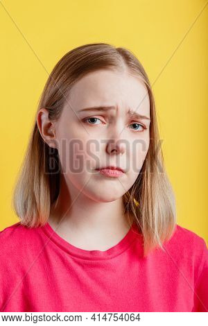 Young woman is upset. Closeup Emotional portrait of teenager girl with grimace of crybaby displeasure sad tired face. Sorry sad lady portrait isolated over yellow color background