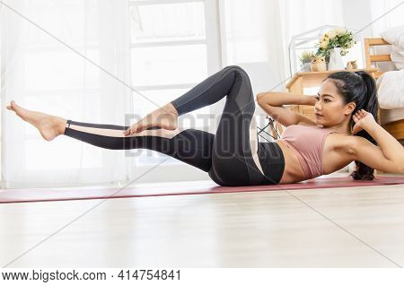 A Beautiful Asian Woman's Fitness At Home Instead Of Going To The Fitness Gym. She Warms Up The Body