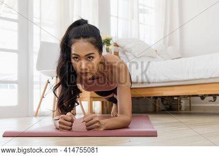 A Beautiful Asian Woman's Fitness At Home Instead Of Going To The Gym. She Doing A Plank On The Yoga