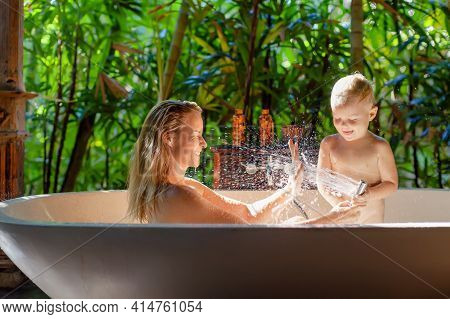 Happy Baby Son With Mother Have Fun In Bath. Playful Woman Spraying Child From Shower In Outside Bat