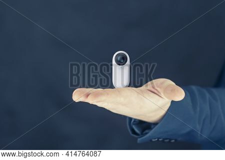 A Man Holds A Compact White 360-degree Action Camera In His Hand