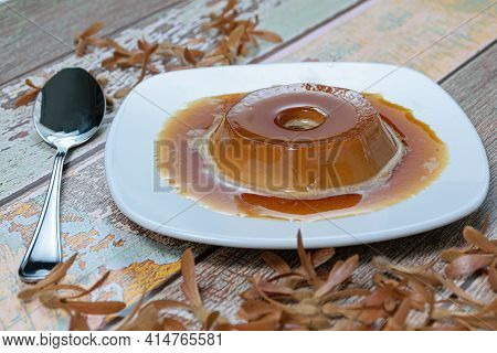 Dulce De Leche Pudding With Caramel Sauce, Next To A Spoon And Flying Seeds (triplaris Americana). A