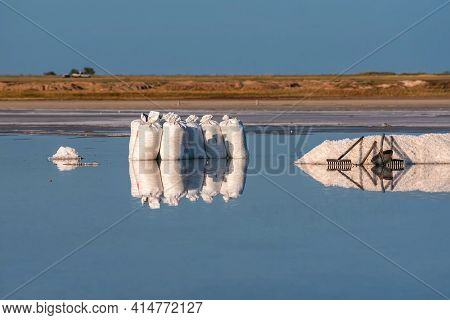 Scenic View Of White Piles Of Salt, Bags, Tools And Their Reflections In The Water Of A Salt Lake Ag