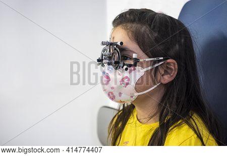 Little Girl Doing Eye Test At Optometrist. Children Caring For Eye Concept