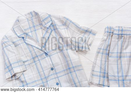 White Cotton Pajamas With Blue Checks Or Stripes, On A White Wooden Background With Copy Space. Nigh