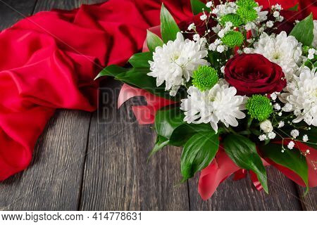 Bouquet Of Scarlet Roses And Chrysanthemums On A Wooden Background And Fabric