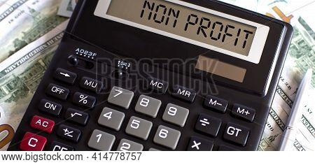 Non Profit On Calculator. Business And Tax Concept On Dollars Background.