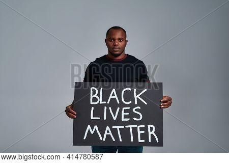 African American Man Holding Anti Racism Poster And Looking At Camera While Posing On Light Backgrou