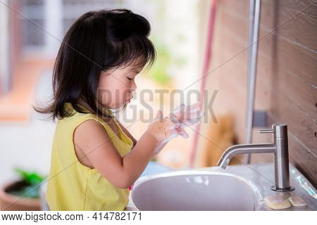 Cute Asian Girl Washed Her Hands With Soap In The White Sink. Children Rub The Bubbles In Their Hand